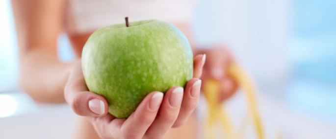 mano mostrando manzana verde
